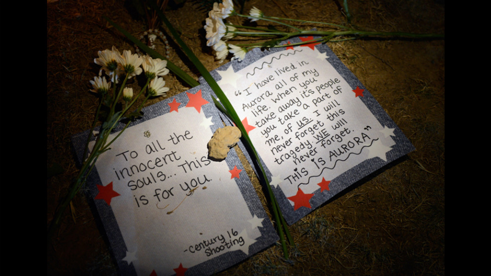 Handwritten consolation letters lie beneath flowers at a makeshift memorial.