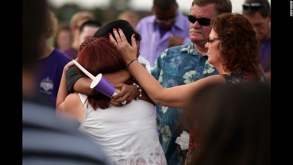 Movie theater shooting victim A.J. Boik's girlfriend, Lasamoa Croft, center, embraces his mother during the memorial service.