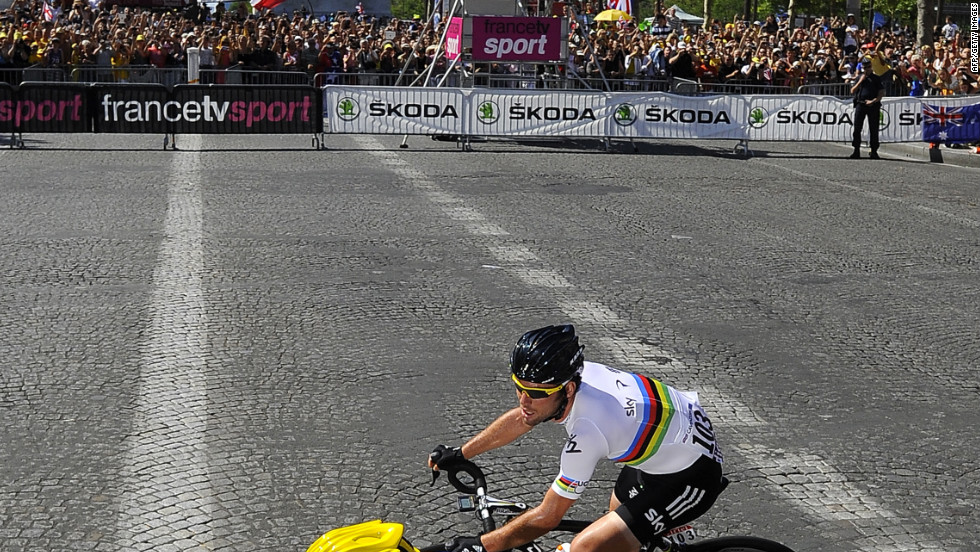 Cavendish and Wiggins, in yellow, ride past the Arc de Triomphe as the three-week race comes to an end in Paris on Sunday.