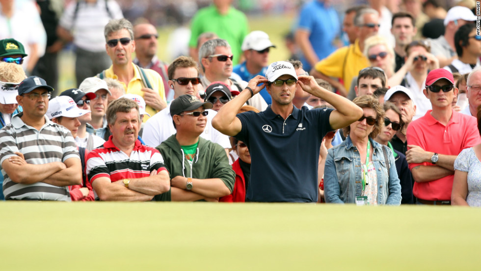 Adam Scott looks at his putting line on a green Sunday.