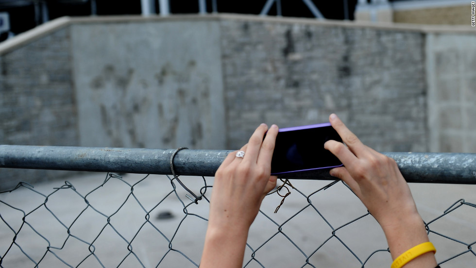 A girl takes a picture at the site where the statue of former Penn State University football coach Joe Paterno stood. It sits empty now after it was removed by workers outside Beaver Stadium on Sunday, July 22.