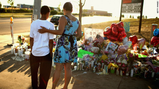 AURORA, CO - JULY 22:  Barb Whitfield (R) and her granson Wanya Whitfield, 15, visit at a makeshift memorial to the vicitims of last weekend's mass shooting at the Century 16 movie theater July 22, 2012 in Aurora, Colorado.  Police in Aurora, a suburb of Denver, say they have James Holmes, 24, in custody after he killed 12 people and injured 59 during a midnight screening of 'The Dark Knight Rises' last Friday.  (Photo by Chip Somodevilla/Getty Images)