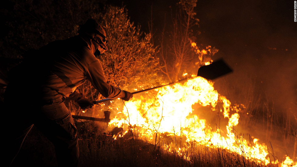 A firefigher tries to extinguish flames in Ller near La Junquera on the Spanish-French border Sunday, July 22.