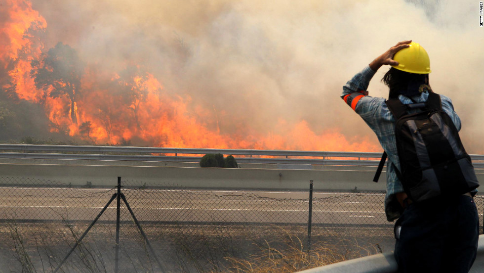 A photographer takes pictures of the wildfire from acros a highway in La Jonquera on Sunday.