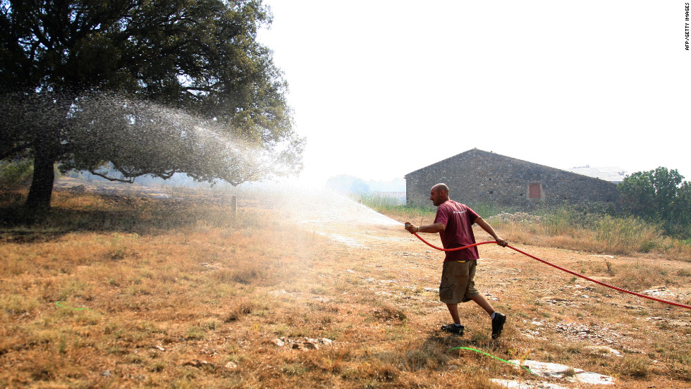 A man waters his yard in an attempt to protect his house from the wildfire raging near Figueras on Monday.