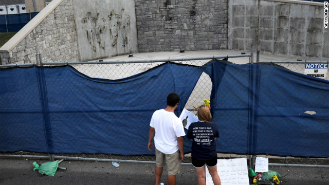 Visitors peer through a tarp covered fence at the location where a statue of Joe Paterno was removed from.
