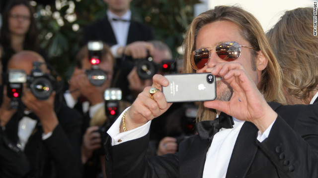 Brad Pitt takes pictures with an iPhone at the 65th Cannes film festival in May.