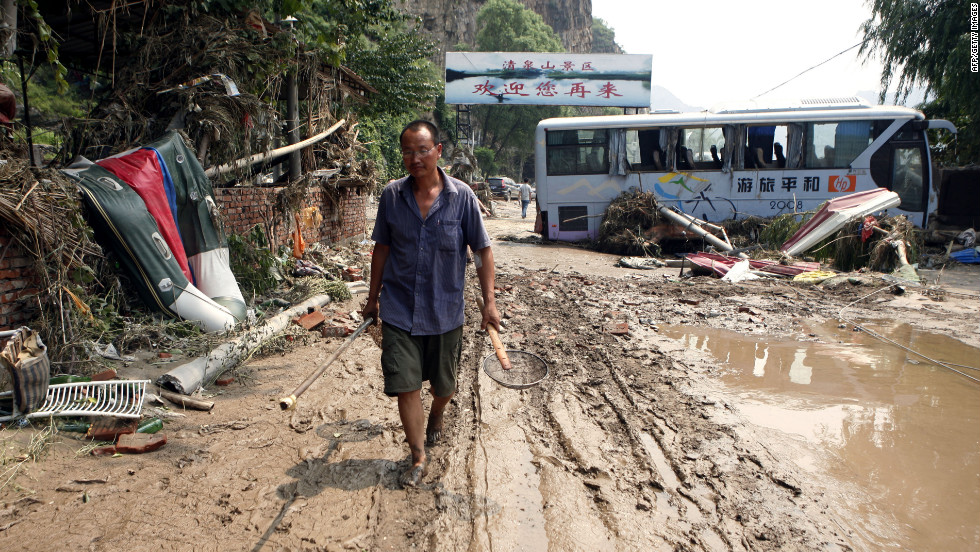 A man slogs through mud past damaged vehicles after flooding Tuesday, July 24, in Laishui, China, north of Beijing. The heaviest rain in 60 years submerged large parts of the Chinese capital.