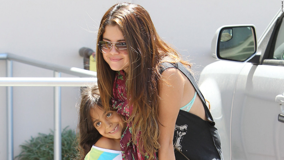 Selena Gomez takes a picture with a fan.