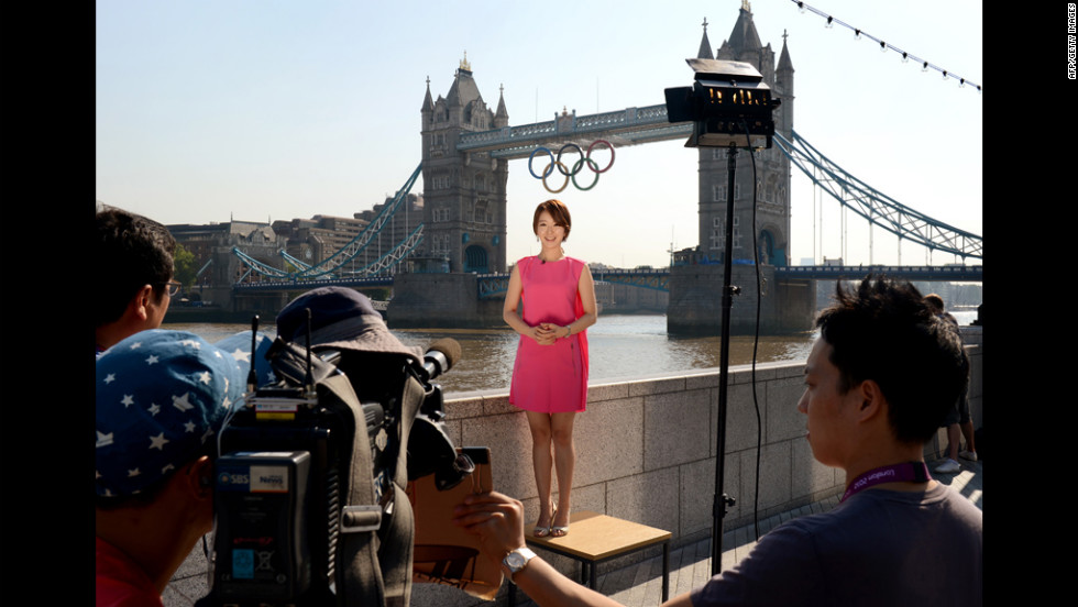 A South Korean news crew reports from in front of the Tower Bridge where Olympics Rings hang.
