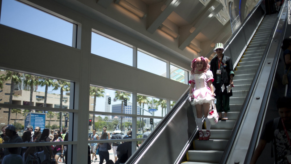 "Madoka Kaname (from ""Madoka Magica"") and Kisuke Urahara (from ""Bleach"") exude a cool otaku vibe as they head to the ground floor of the San Diego Convention Center."
