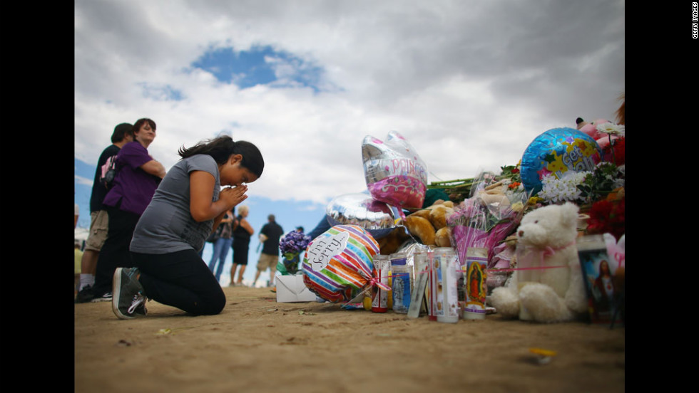 Yvonne Amaro, 9, prays for those injured and killed as she visits the memorial on Wednesday.