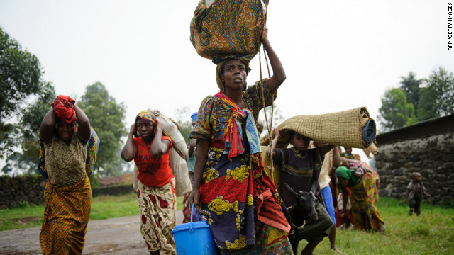 Congolese people flee a clash between M23 rebels and the Congolese army on the edge of the village of Rugarion on Thursday.