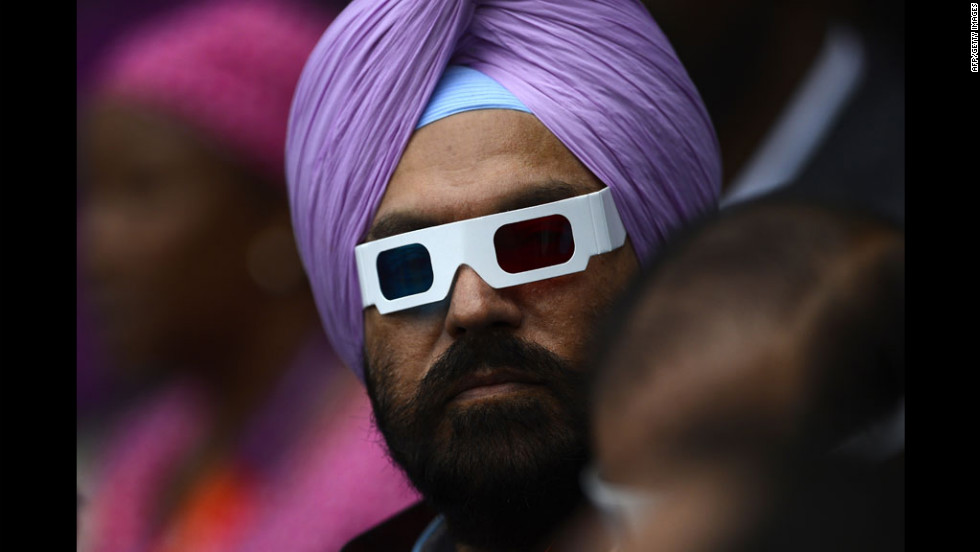 A man wearing glasses waits for the start of the opening ceremony.