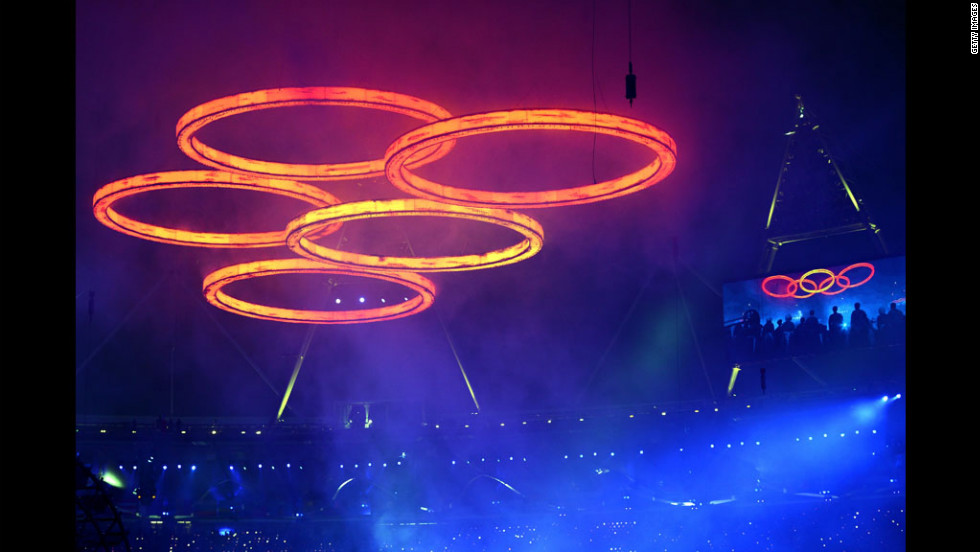The Olympic rings are assembled above the stadium in a scene depicting the Industrial Revolution.