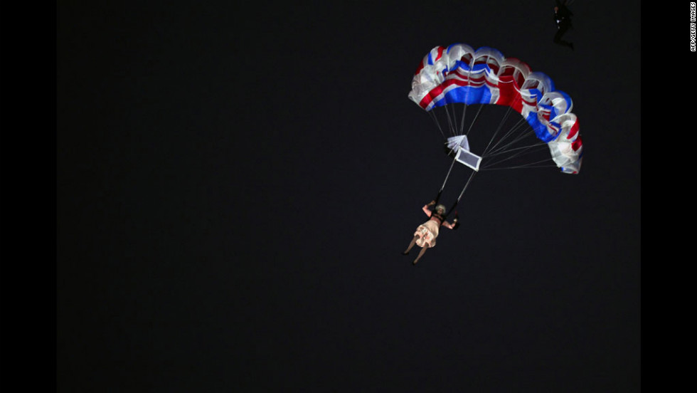 An actor dressed to resemble Britain's Queen Elizabeth II parachutes into the stadium.