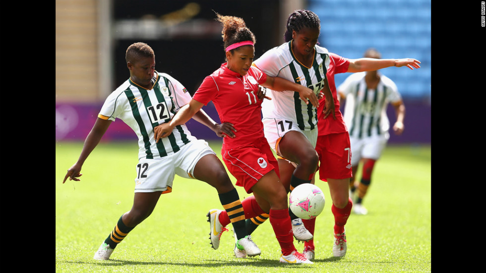 Desiree Scott of Canada and Andisiwe Mgcoyi of South Africa fight for the ball during a first-round women's soccer game.