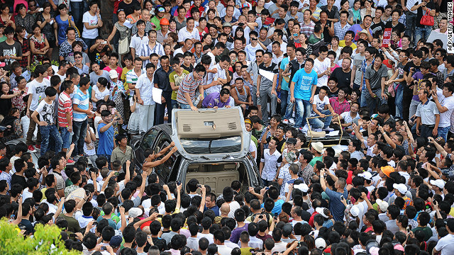 Demonstrators protesting industrial pollution destroy a car in the compound of local government offices in Qidong, China.