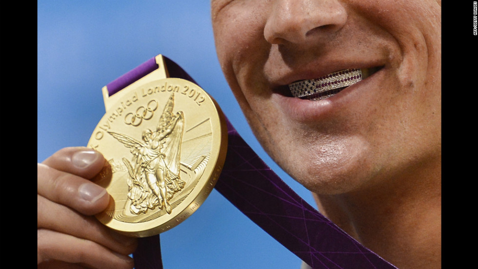 Lochte poses with medal on Saturday. His dental braces bear the U.S. flag.