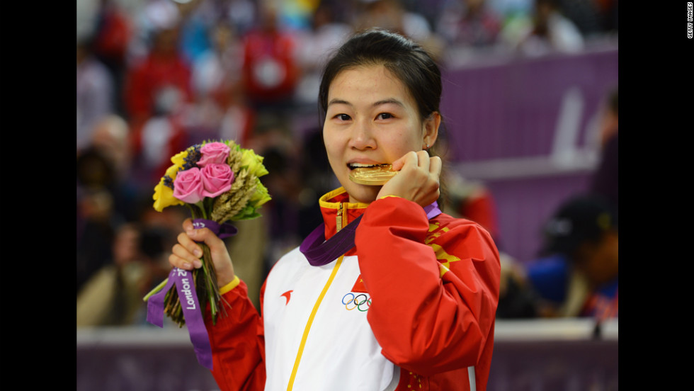 Having won the first gold medal of the Games, Siling Yi of China celebrates her victory during the ceremony for the women's 10-meter air rifle shooting.