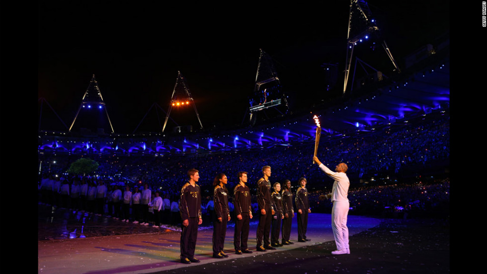Torchbearer Sir Steve Redgrave hands the Olympic flame over to the seven young athletes who represent Britain's hopes for the next Olympics.