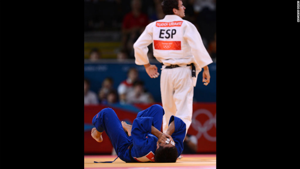 Francesco Faraldo of Italy, in blue, reacts after losing against Sugoi Uriarte of Spain, in white, during their men's judo event.