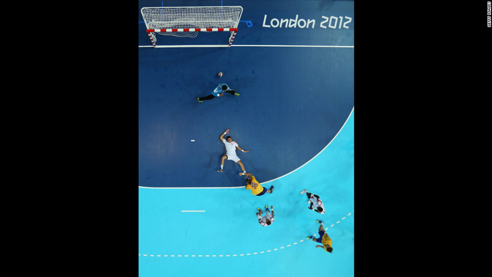 Sweden's Andreas Nilsson, No. 35 in yellow, scores past Issam Tej and goalkeeper Marouen Maggaiz of Tunisia during a men's handball preliminary match.