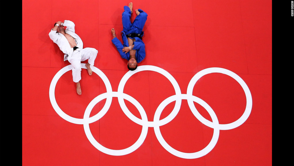 Poland's Pawel Zagrodnik, left, and Masashi Ebinuma of Japan rest on the mat after their men's under 66-kilogram judo match.