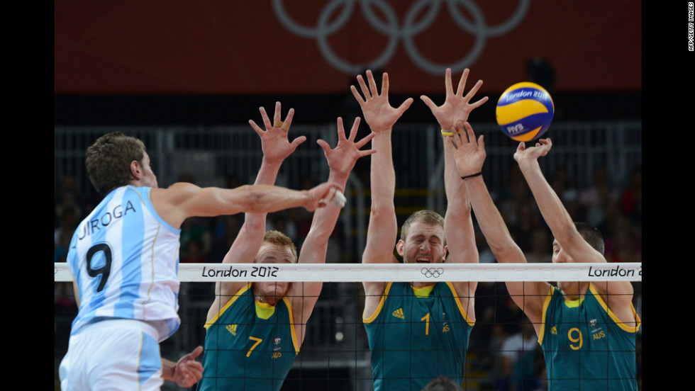 Argentina's Rodrigo Quiroga, left, spikes as Australia's team attempts to block during men's volleyball action between Australia and Argentina.