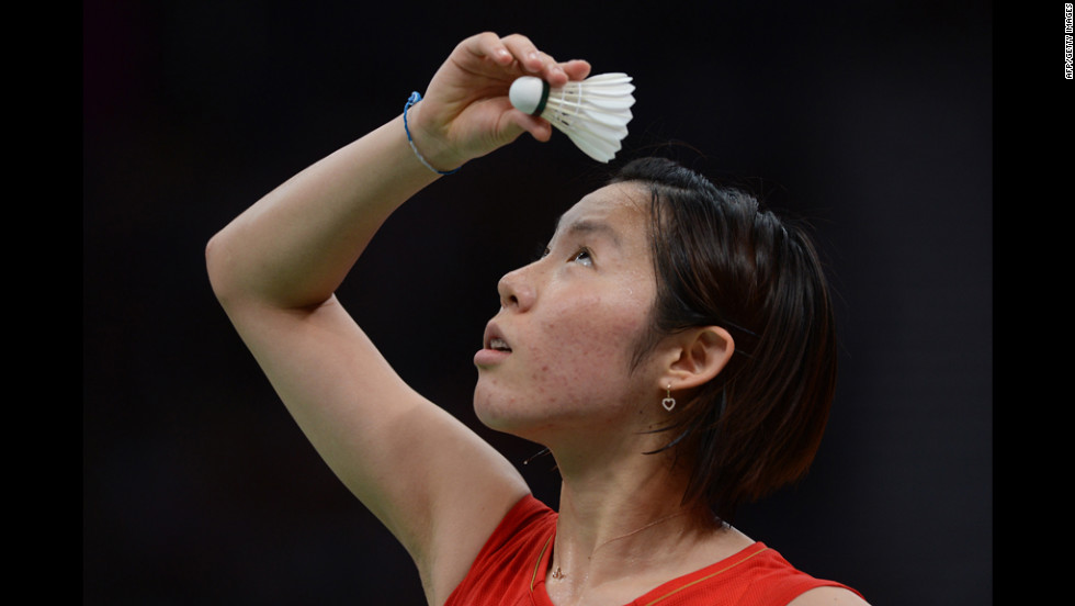 Japan's Sayaka Sato reads the directions on the shuttlecock before a serve.