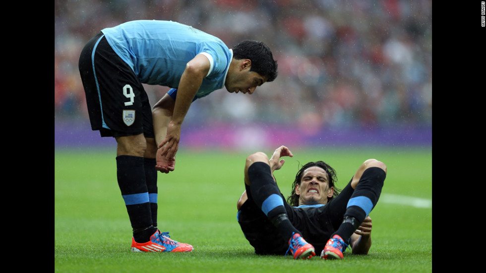 Edinson Cavani of Uruguay attempts to set a world sit-up record. A teammate counts off beside hm.