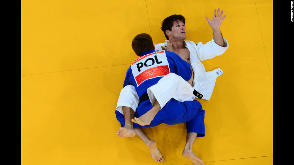 Leandro Cunha of Brazil, in white, competes with Pawel Zagrodnik of Poland, in blue, during their men's 66 kilogram judo event.