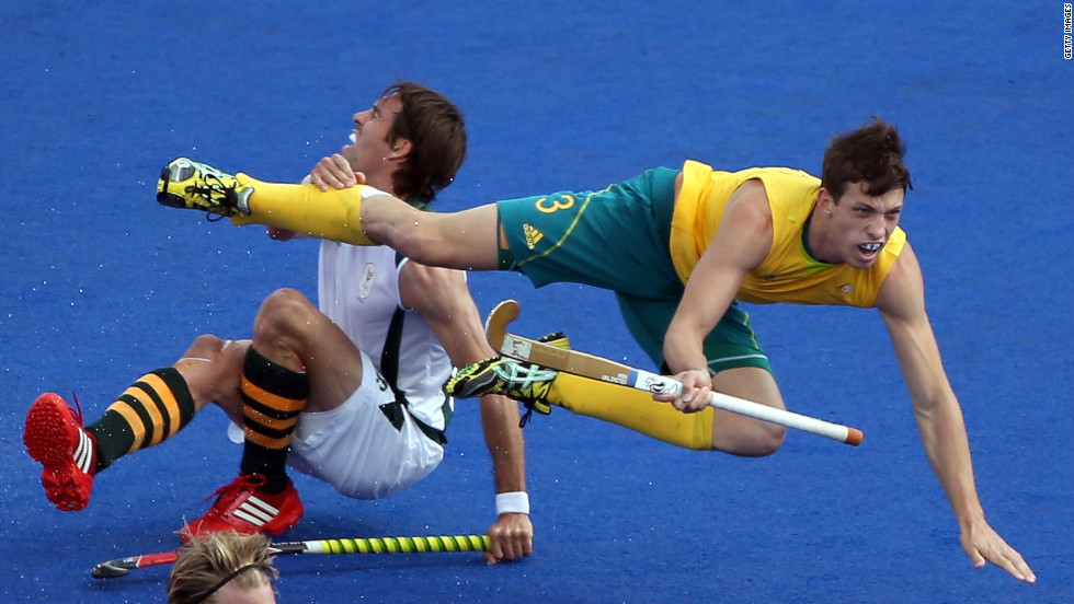 Simon Orchard of Australia fights for the ball against Thorton McDade of South Africa during the men's field hockey match Monday.