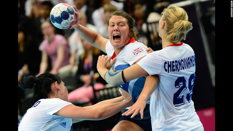 Britain's leftback Ewa Palies, center, fights for possession during the women's preliminaries Group A handball match against Russia on Monday.