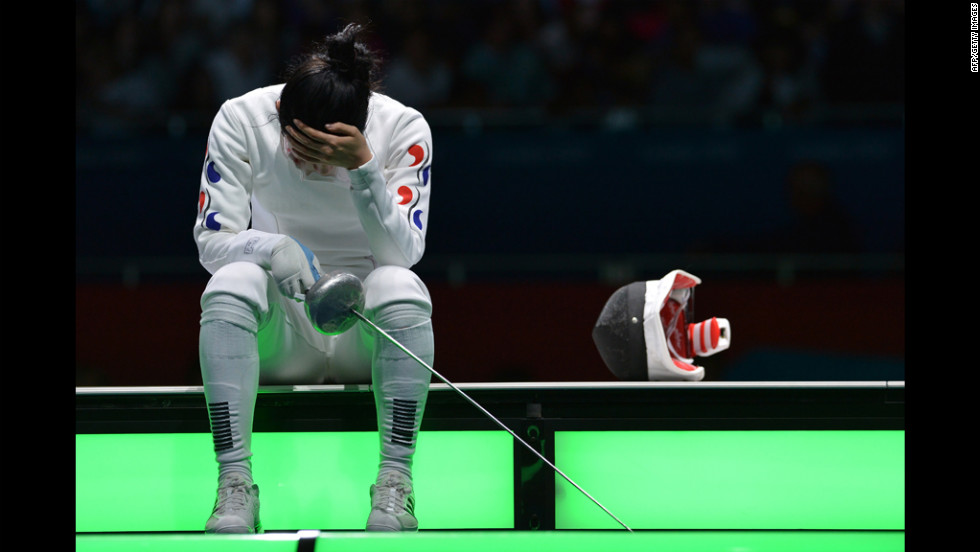 South Korea's  A Lam Shin sits on the fencing field at the end of her women's epee semifinal bout against Germany's Britta Heidemann. The distraught South Korean eventually had to be escorted away.