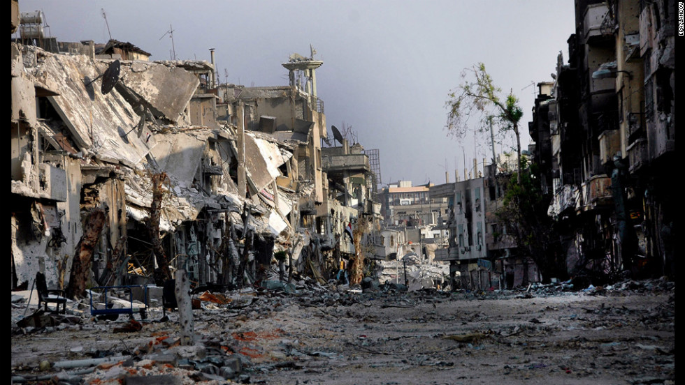 A photo released by Syrian Arab News Agency depicts damaged buildings in Homs on Monday, July 30.