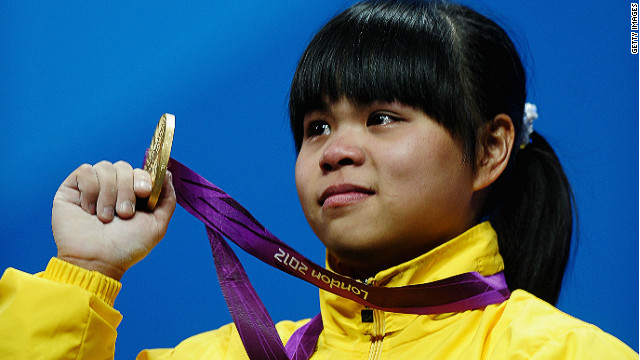Zulfiya Chinshanlo of Kazakhstan stands with her gold medal on the podium after the Women's 53kg Weightlifting event.