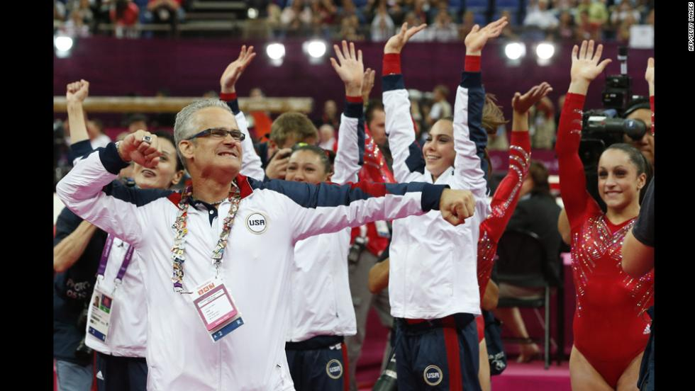 U.S. women's gymnastics coach John Geddert celebrates with his team after they won the gold in the team competition Tuesday.