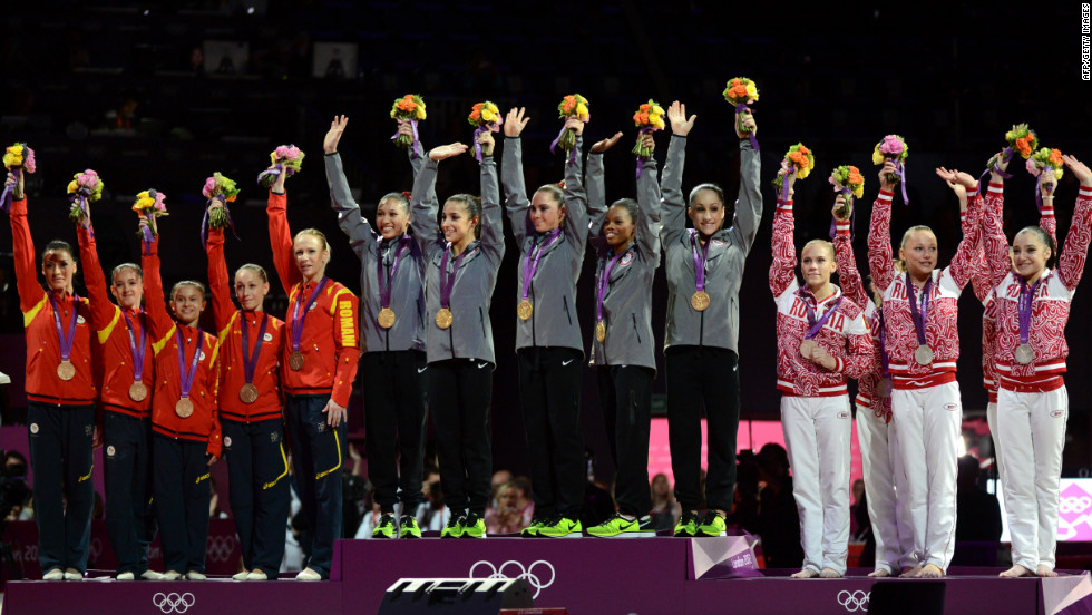 Gold winners Team USA, center, silver winners Team Russia, right, and bronze winners Team Romania celebrate on the podium of the women's team competition of the gymnastics event.