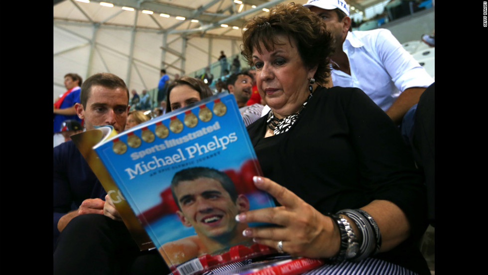Debbie Phelps, the mother of swimming star Michael Phelps, reads Sports Illustrated magazine before Tuesday's evening competition session at the 2012 Olympic Games in London.