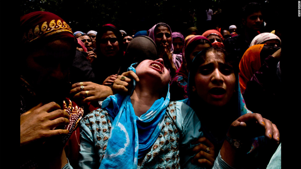 Kashmiri Muslim neighbors console a relative of Auqib Ahmad Bhat as she mourns during his funeral Tuesday in Balpora, Indian-administered Kashmir. The circumstances of Bhat's death are in dispute.
