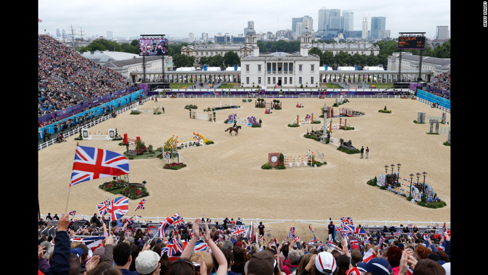 Fans wave Union Jack flags as Britain's William Fox-Pitt, riding Lionheart, performs Tuesday in the show-jumping qualifying equestrian event at Greenwich Park.