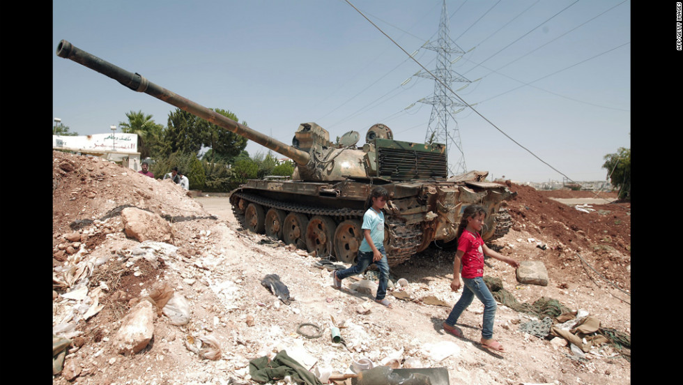 Syrian girls on Wednesday walk past a Syrian army tank captured two days earlier by rebel fighters at a checkpoint in the village of Anadan. The strategic checkpoint secures the rebel fighters free movement between the northern city of Aleppo and Turkey.