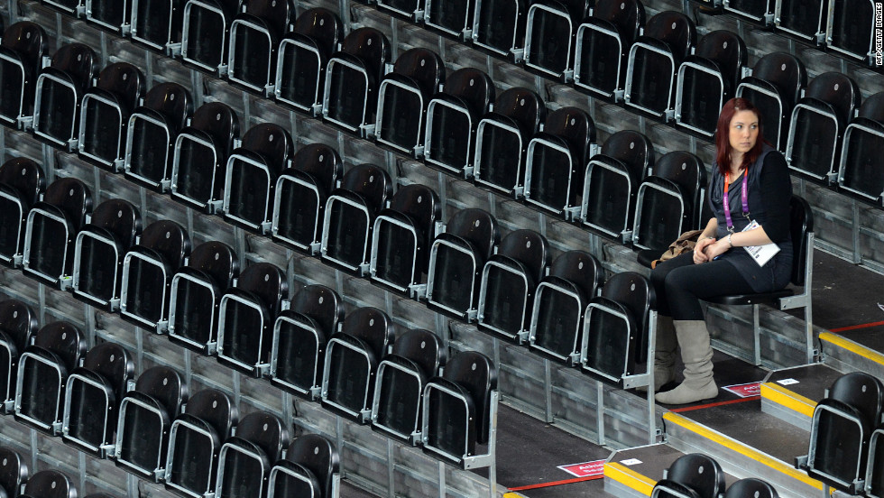 A woman sits in empty stands Wednesday during a women's preliminary volleyball match between the Dominican Republic and Japan.