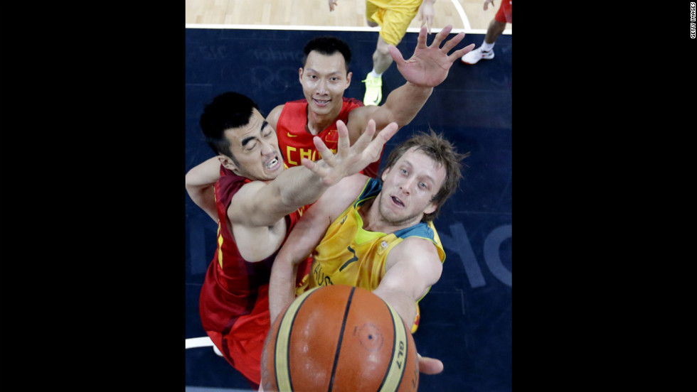 Australia's Joe Ingles tries to score against China's Wang Zhizhi, left, and Yi Jianlian during a men's basketball preliminary round.