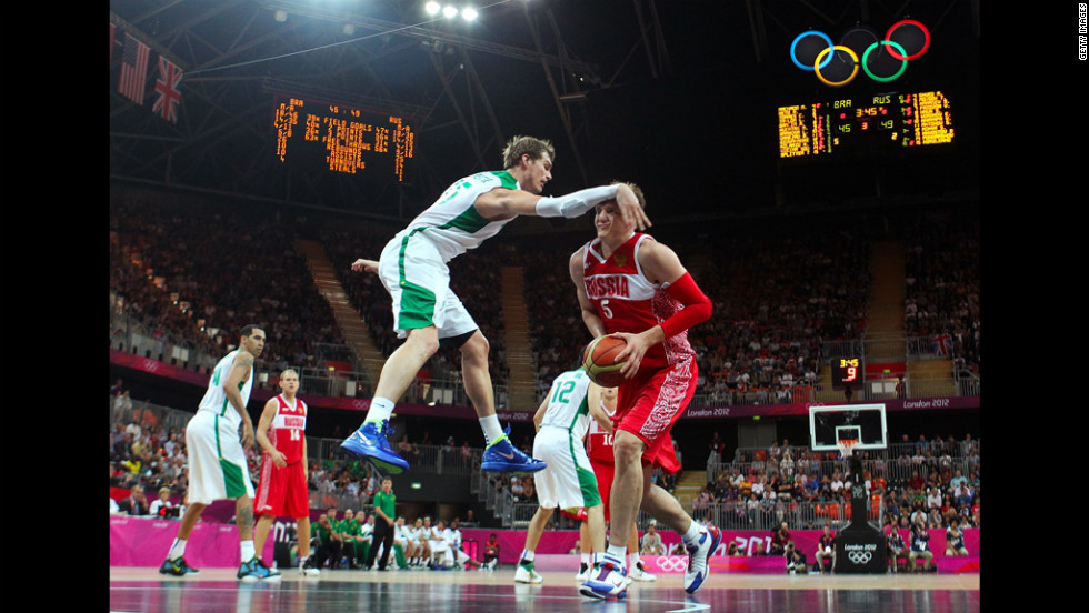 Russia's Timofey Mozgov receives an arm to the head as he looks to shoot against Brazil's Tiago Splitter in the second half of the men's basketball preliminary round match.