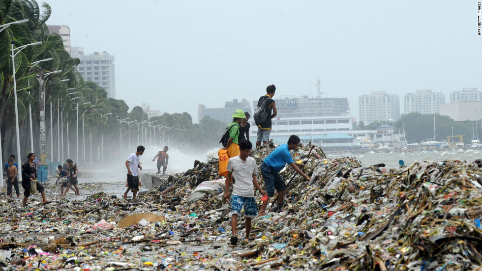 People pick up recyclable materials among the trash washed ashore along's Manila's Roxas Boulevard.
