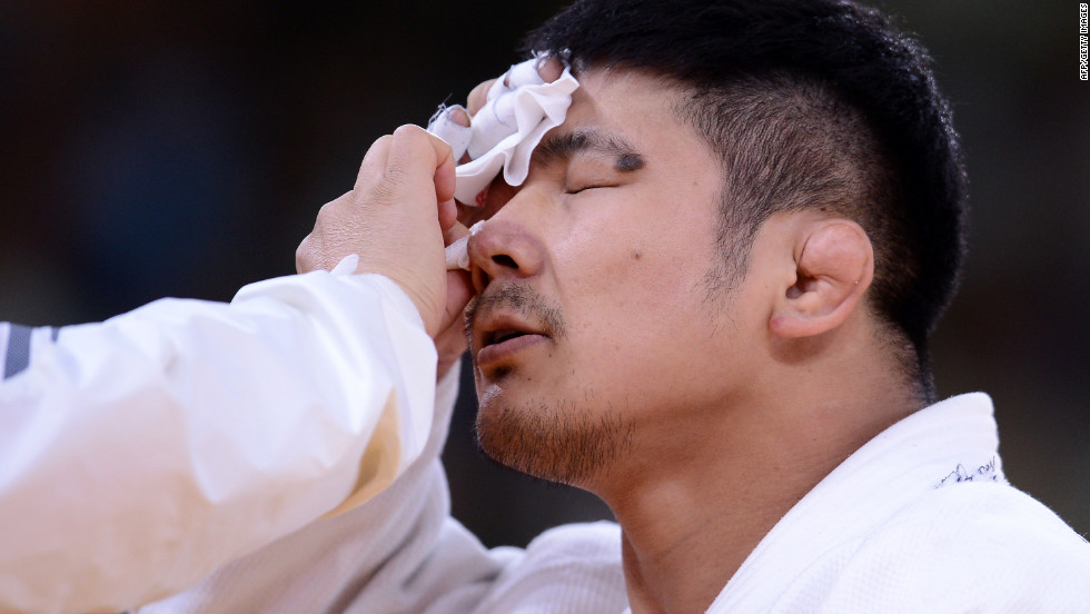 South Korea's Hwang Hee-Tae gets treated for an injury during a men's under 100-kilogram judo contest match.