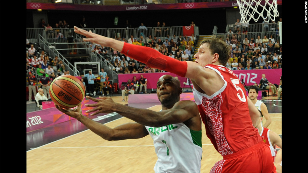 Brazilian forward Larry Taylor, left, tries to get past Russian center Timofey Mozgov, right, during the men's preliminary round basketball match.