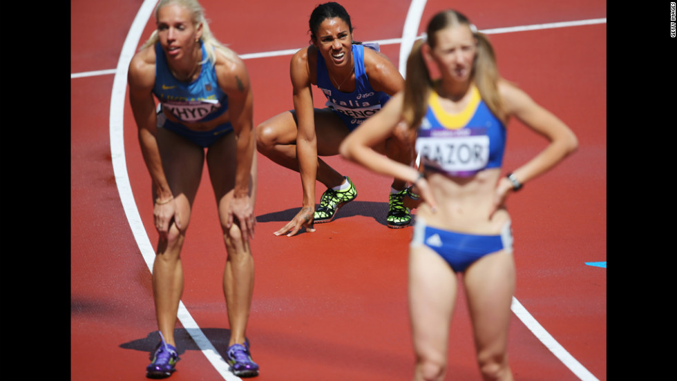 Italy's Libania Grenot, center, checks out the scoreboard after the women's 400-meter heats.